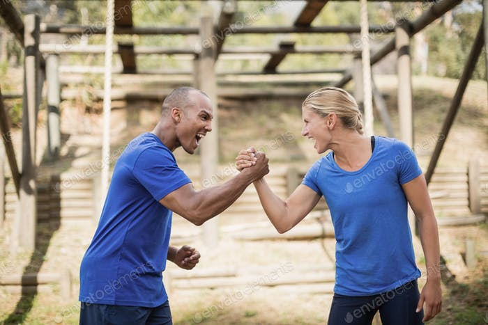 Fit man and woman greeting each other during obstacle course