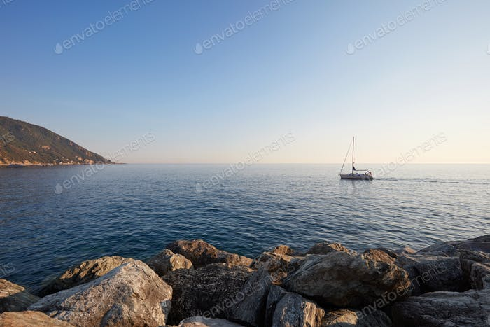 Mediterranean blue, calm sea and rocks with boat, clear sky