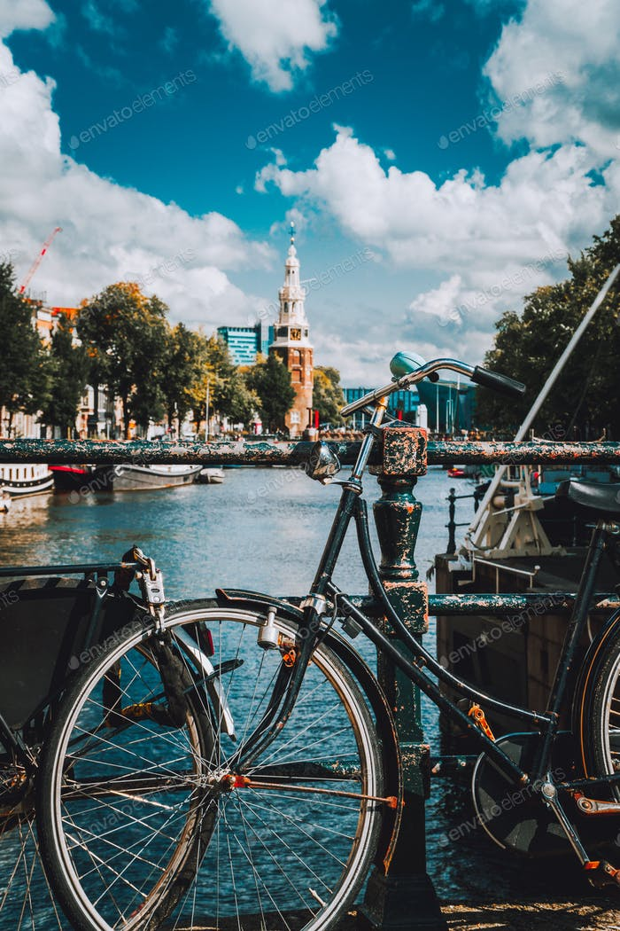 Close-up of Bike parked on a bridge in Amsterdam, Netherlands. Typical cityscape with Amstel river