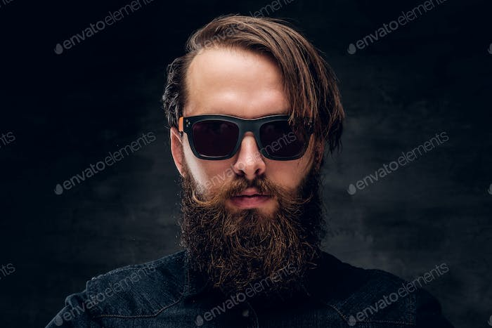 Attractive bearded man in sunglasses over dark background.