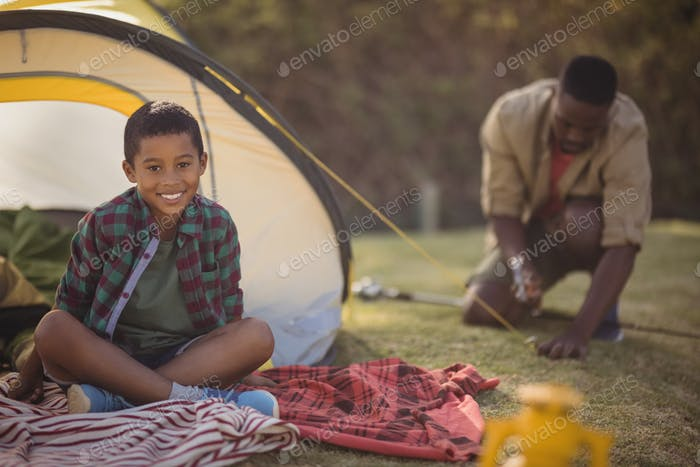 Smiling boy sitting in tent