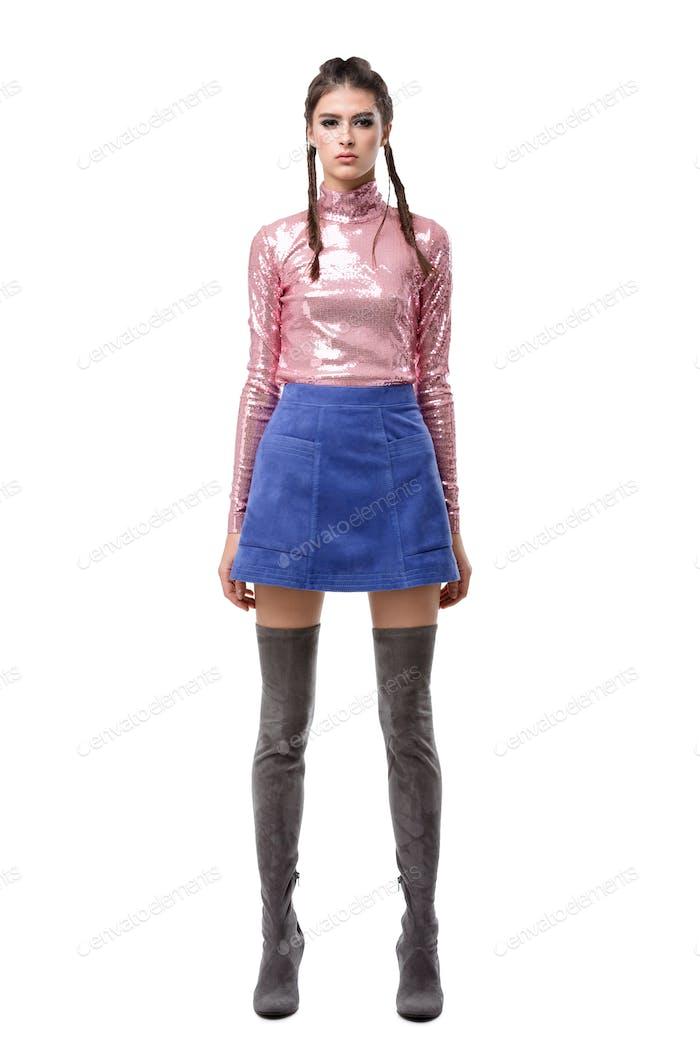 Hübsche Dame stehend in blauem Rock und rosa Top mit Pailletten und kniehohen Stiefeln auf weißem Hintergrund