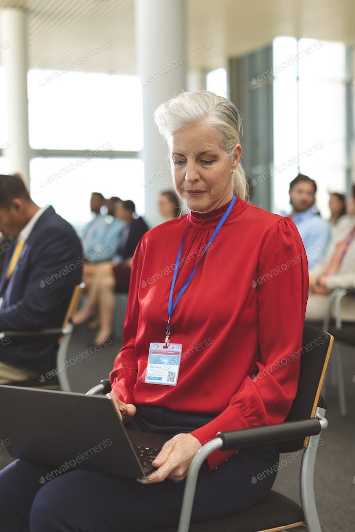 Front view of mature Caucasian businesswoman using laptop during seminar in office building