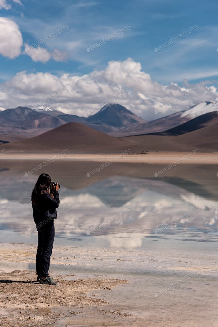 Woman with a camera photographing a volcano