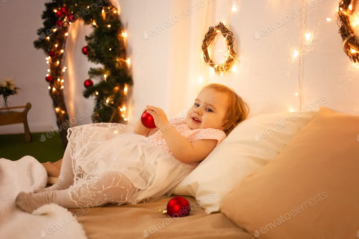 A little girl in a Christmas photo studio. Boke, yellow lights, happy baby