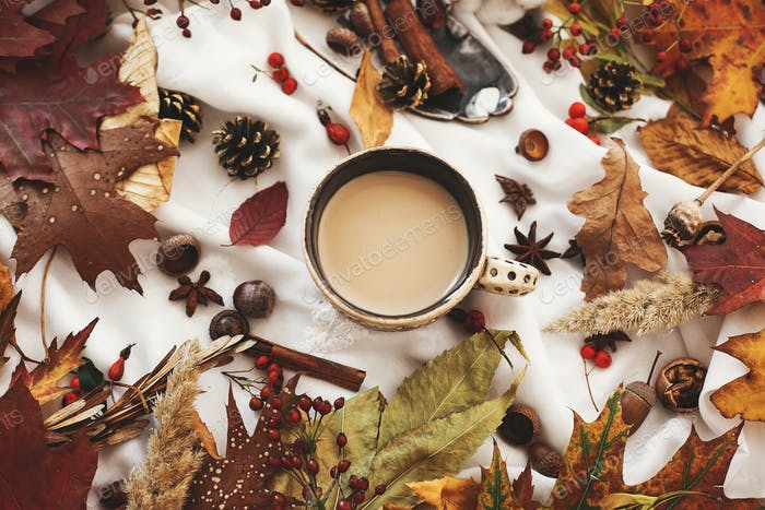 Autumn flat lay, cozy inspirational image.Coffee cup with  fall leaves
