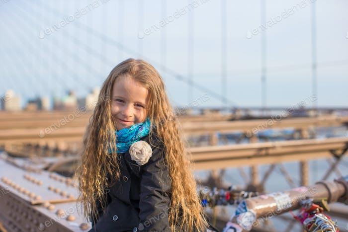 Adorable little girl sitting at Brooklyn Bridge