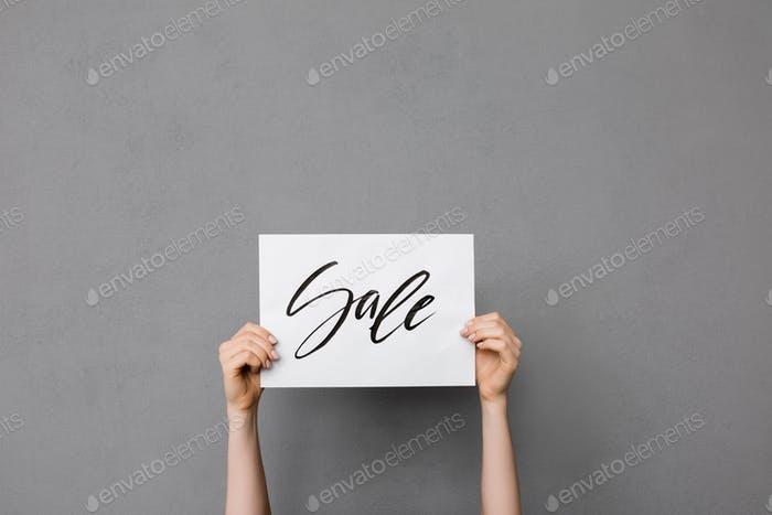 Beautiful photo of woman hands up that holding postcard on gray background