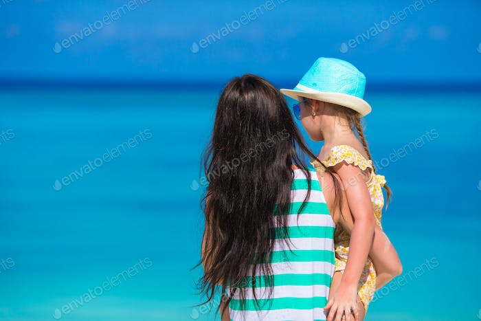 Little girl and young mom during beach vacation