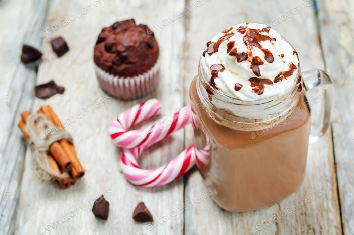 Hot dark chocolate with whipped cream and chocolate cakes
