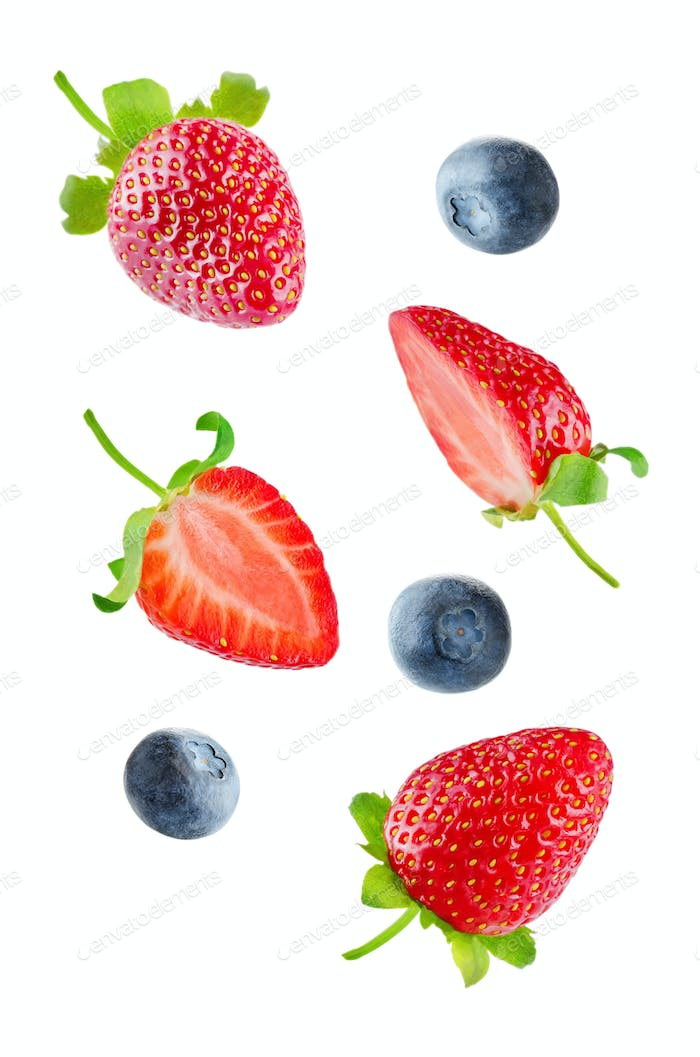 Fresh flying strawberries and blueberries isolated