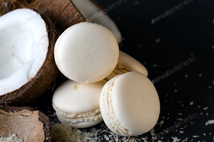 Coconut halves with white macaroons on dark background minimal creative concept.