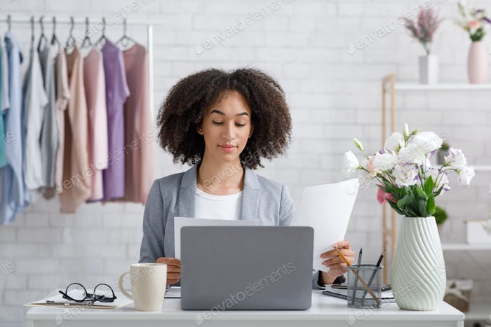 Showroom and office at home. Busy african american lady working with documents near laptop