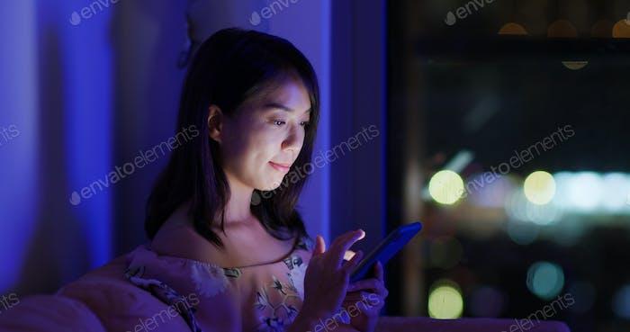 Frau Blick auf das Handy über Nacht