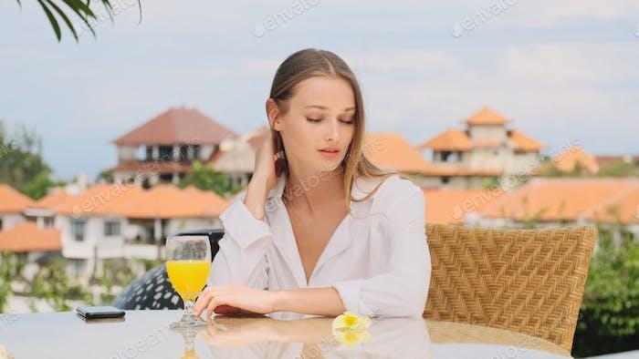 Красивая девушка в пижаме мечтательно мечтательно завтракая на террасе с удивительным видом