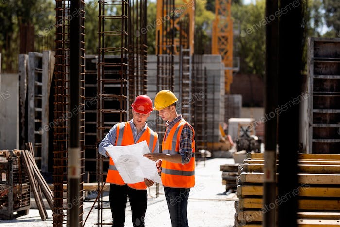 Construction manager and engineer dressed in orange work vests and hard helmets explore construction
