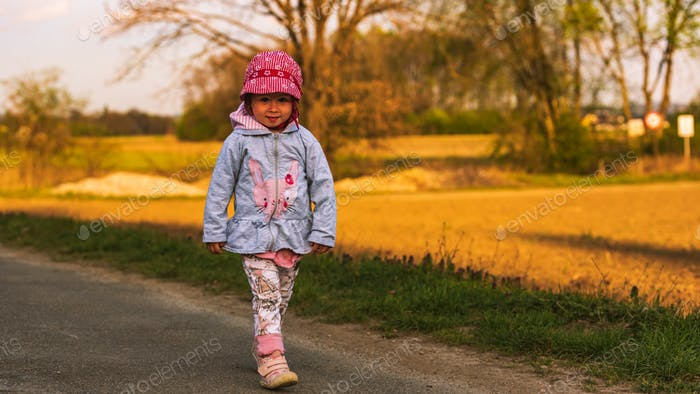 Cute little girl having fun at countryside portrait on sunset