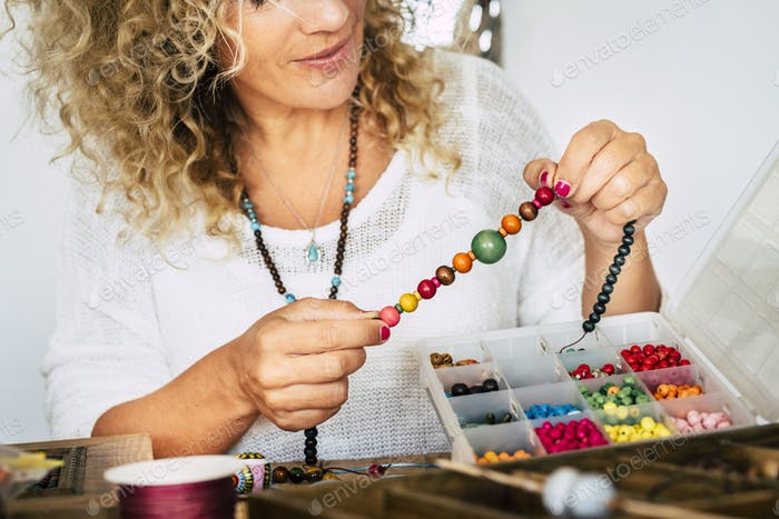 Portrait of adult woman creating beads bracelets and necklace at home for new modern business