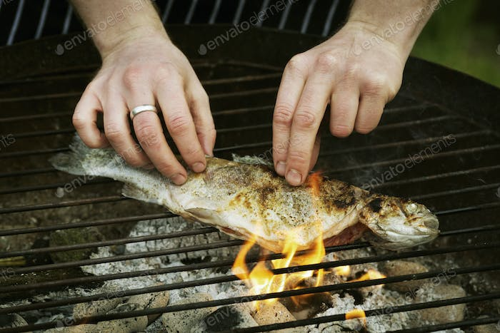 Chef grilling a whole fish on a barbecue.