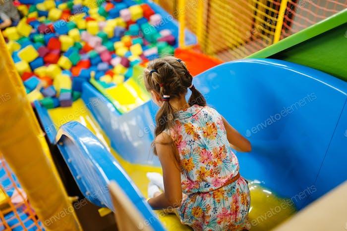 Kleines Mädchen Reiten auf Kunststoff Kinder Rutsche, Spielzimmer