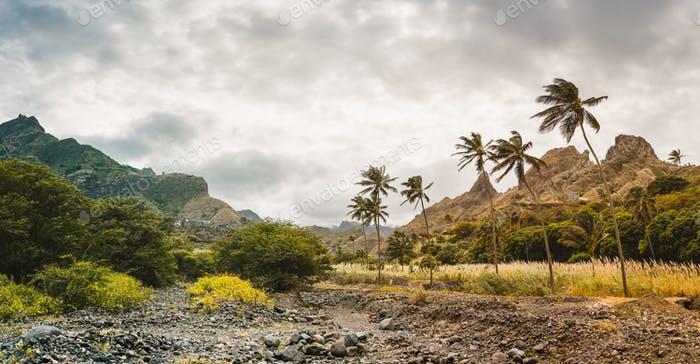 Panorama of dried-up stream surrounded by fertile green valley and rugged cliffs. Santo Antao, Cabo