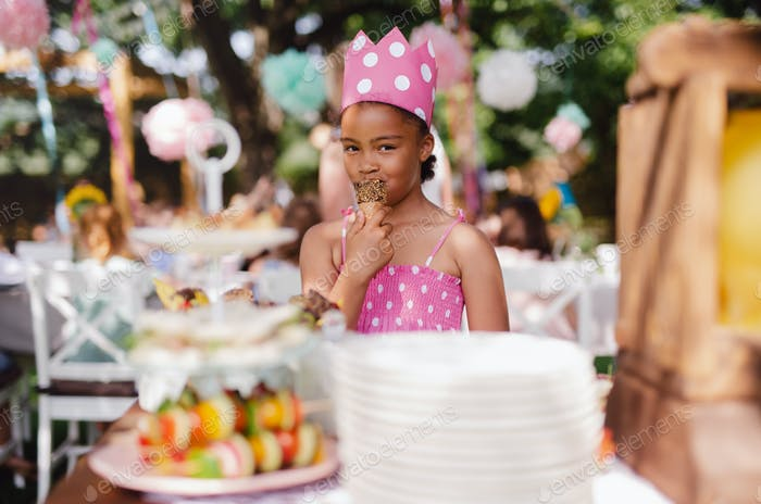 Small girl standing outdoors in garden in summer, birthday celebration concept.