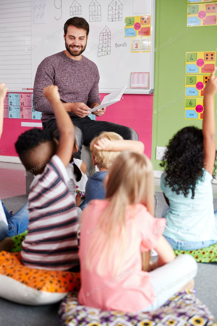 Elementary Pupils Raising Hands To Answer Question As Male Teacher Reads Story In Classroom