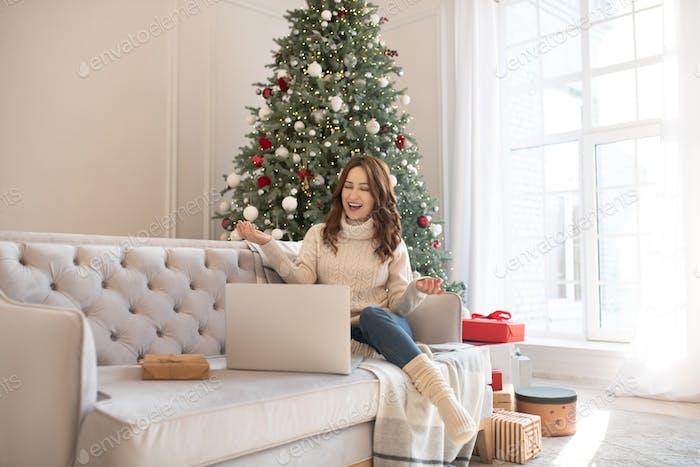 Dark-haired woman near christmas tree having a video call