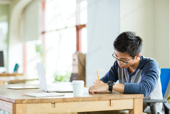 Young serious asian man writing in notebook and using laptop