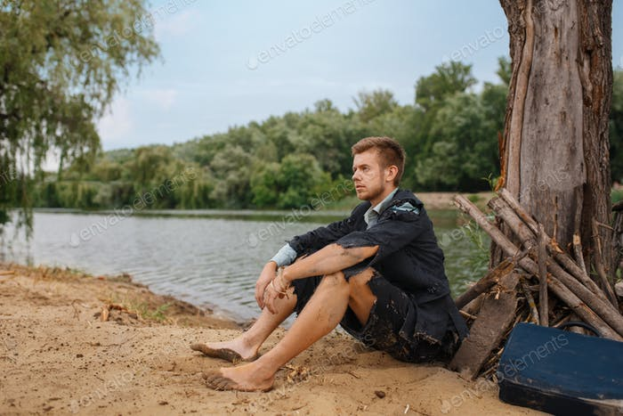 Businessman sitting on the sand, lost island