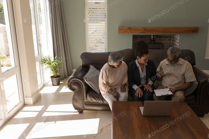 Man signing property contract with real estate agent and senior woman in living room at home