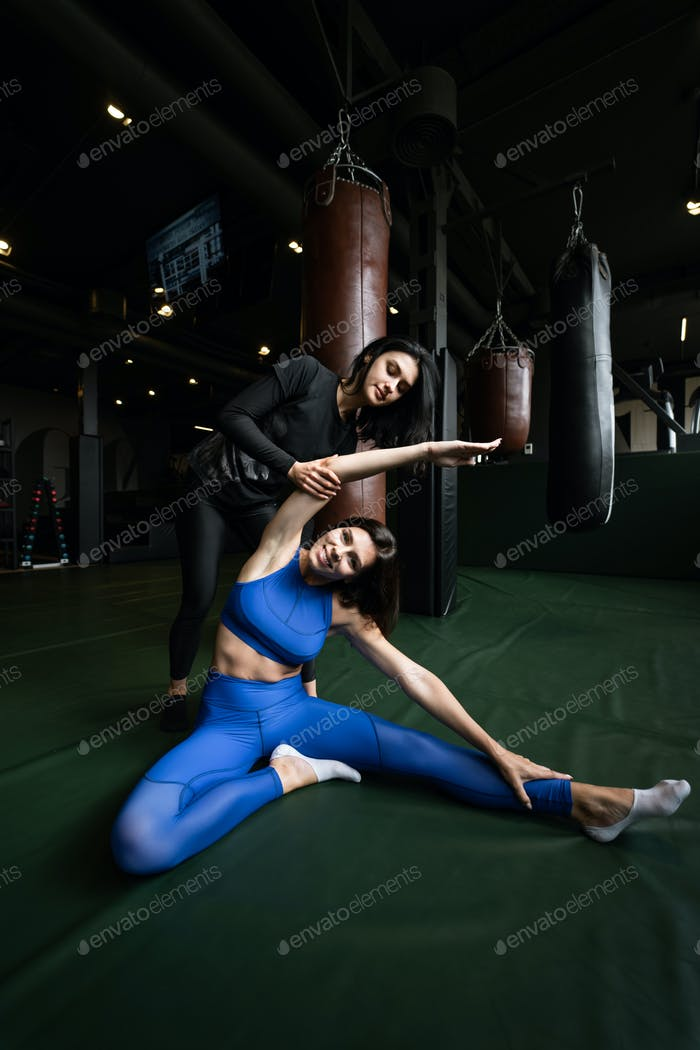 Two beautiful young girls doing fitness in a gym. Stretching the muscles of the legs and arms