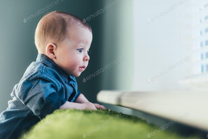 Newborn baby boy on green carpet closeup