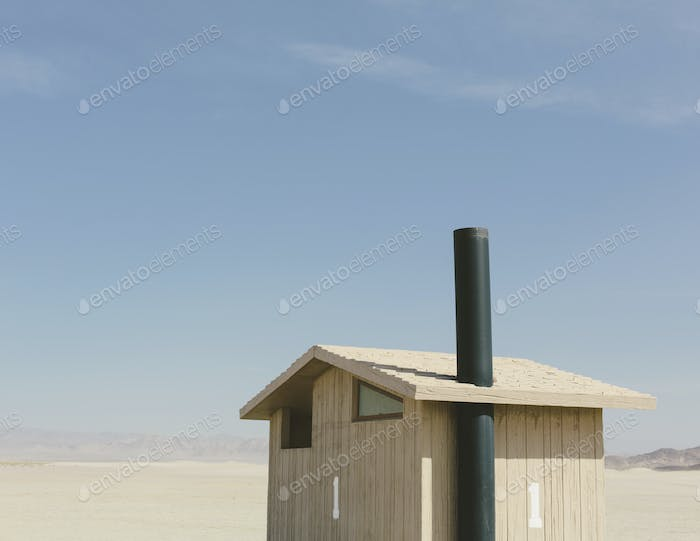 Restroom in a vast desert landscape. A small building.