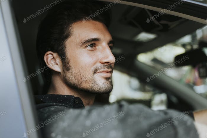 Handsome male driver sitting in a car