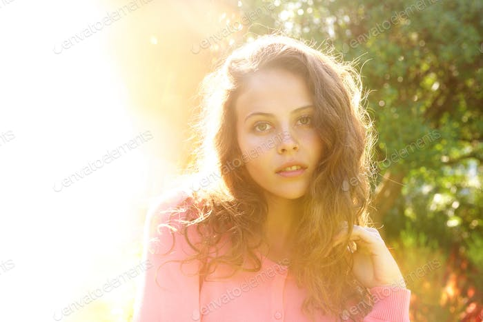 Beautiful woman outside with hand in hair in bright sunlight