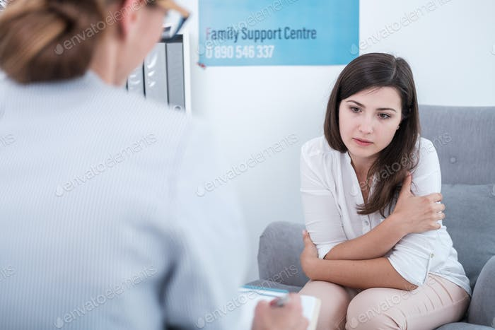 Worried woman during meeting with psychologist in the family sup