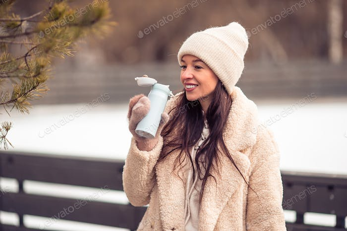 Smiling young girl skating on ice rink outdoors