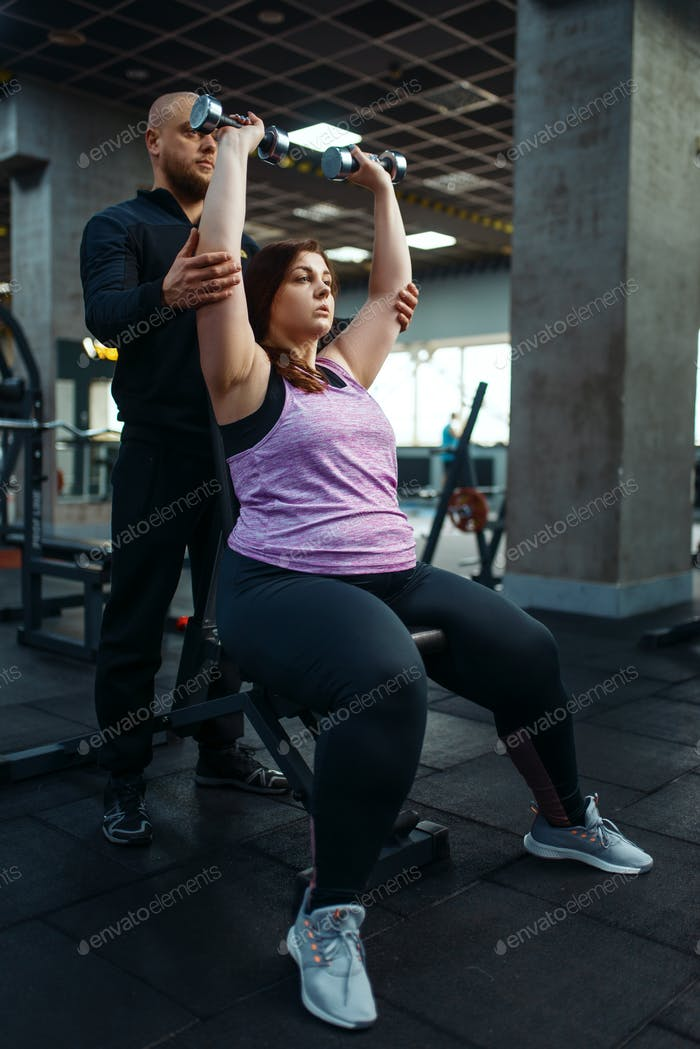 Overweight woman, exercise with dumbbells, trainer