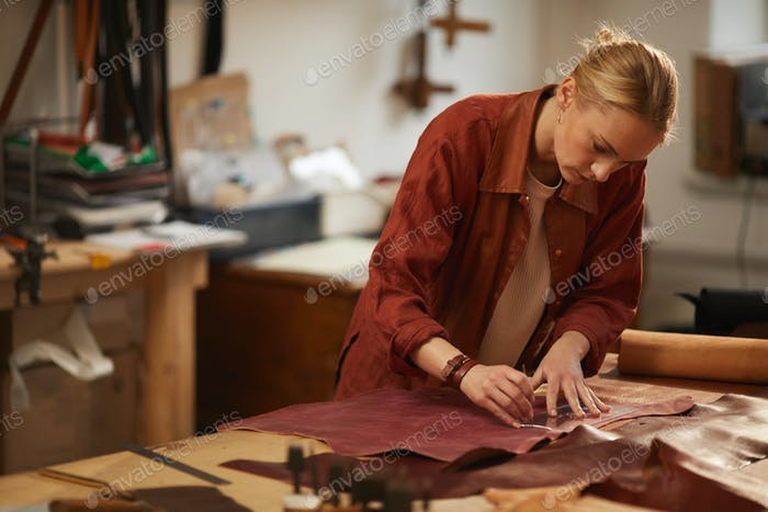 Young Craftswoman Cutting Out Leather