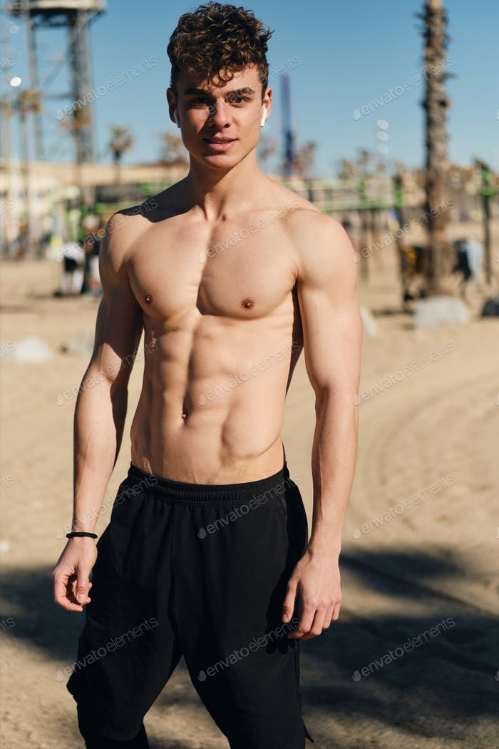 Young handsome man with naked torso confidently looking in camera after workout outdoor
