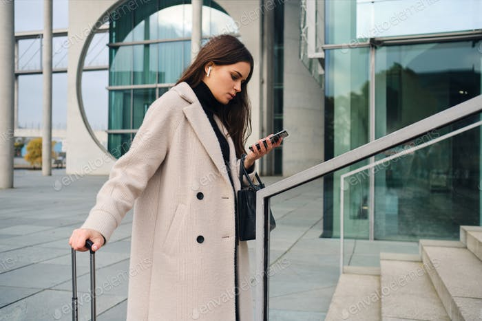 Side view of young businesswoman in coat confidently using cellphone waiting on street with suitcase