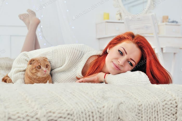 Beautiful young woman with red cat. The concept of Christmas. Ch