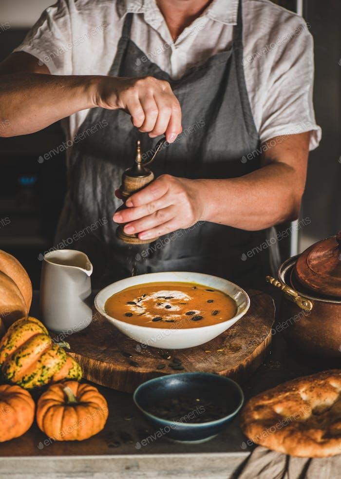 Frau in grauer Schürze Putting Pfeffer Kürbis-Sahnesuppe