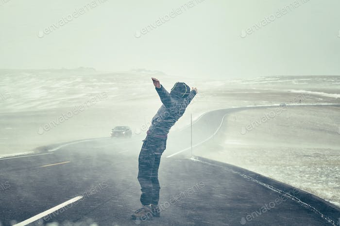 Woman tries to stand against snow flurry seen through a windshie