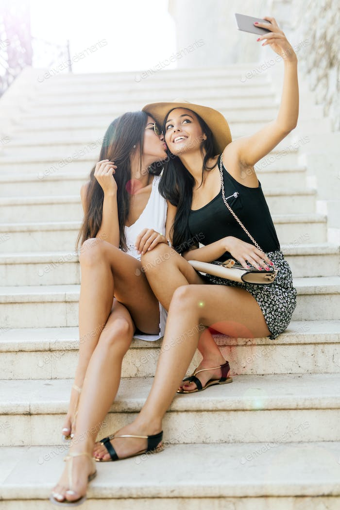 Two young attractive women taking selfies