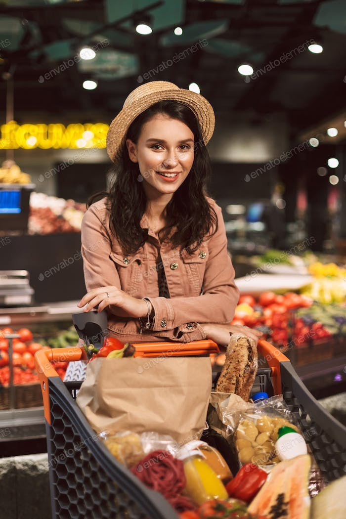 Beautiful smiling girl in hat leaning on trolley full of product