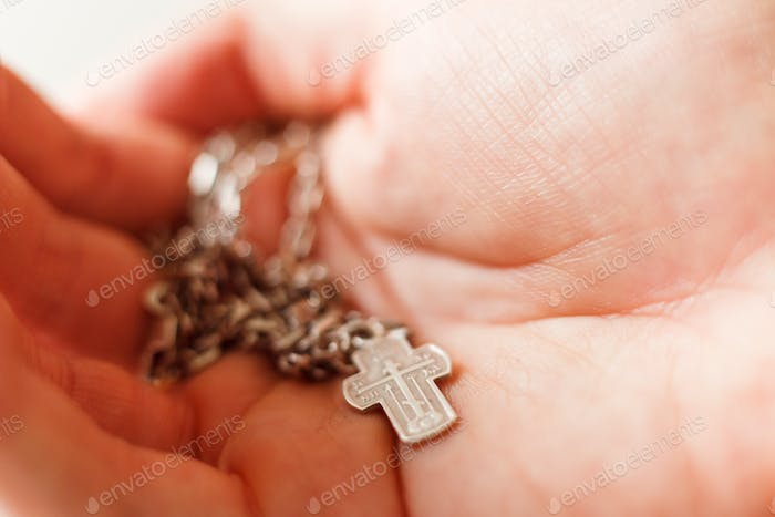 Silver cross in the hand with focus on the cross, shallow DOF