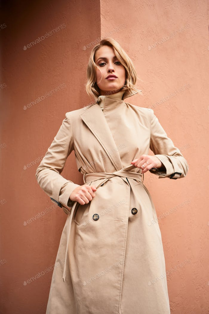 Beautiful casual blond girl in beige trench coat confidently looking in camera outdoor