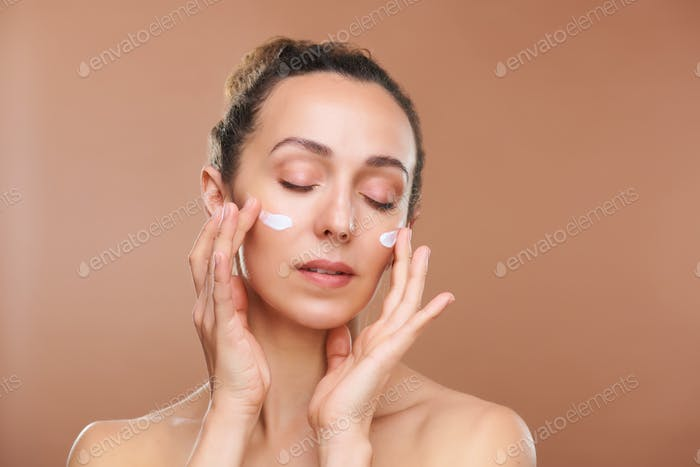 Pretty young woman with her eyes closed applying new lifting cream on face